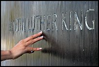 Hand touching the letters Martin Luther King in flowing water. Montgomery, Alabama, USA