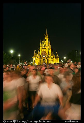 Crowds walking away from Cinderella Castle at night. Orlando, Florida, USA