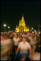 Crowds walking away from Cinderella Castle at night. Orlando, Florida, USA (color)