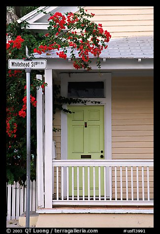 Pastel-colored house, tropical flowers, street sign. Key West, Florida, USA