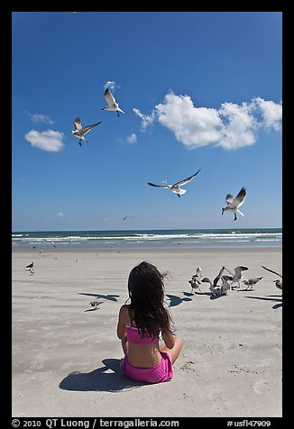 Girl sitting on beach with birds flying, Jetty Park. Cape Canaveral, Florida, USA (color)