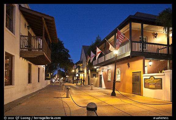 Old street and historic buildings with flags by night. St Augustine, Florida, USA (color)