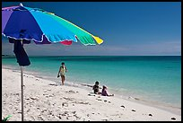 Beach with unbrella, children playing and woman strolling,. The Keys, Florida, USA (color)
