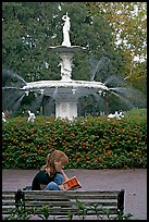 Woman sitting on bench with book in front of Forsyth Park Fountain. Savannah, Georgia, USA