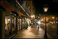 Restaurant, lamps, and sidewalk of River Street by night. Savannah, Georgia, USA