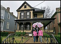 African American family with umbrella in front of Birth Home of Martin Luther King Jr. Atlanta, Georgia, USA (color)