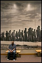 African American man sitting in front of march mural inside Martin Luther King, Jr. Visitor Center. Atlanta, Georgia, USA