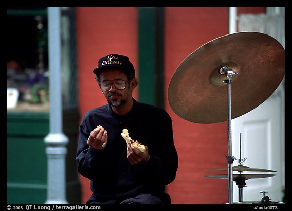 Street musician taking a lunch break, French Quarter. New Orleans, Louisiana, USA (color)