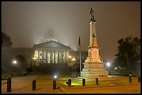 Monument to Confederate soldiers and state capitol at night. Columbia, South Carolina, USA (color)