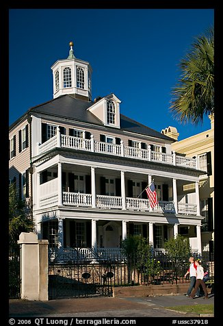 Couple walking in front of antebellum house. Charleston, South Carolina, USA (color)