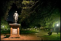 Park with statue and couples sitting on public benches at night. Charleston, South Carolina, USA ( color)