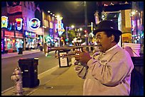 African-American man playing trumpet on Beale Street by night. Memphis, Tennessee, USA