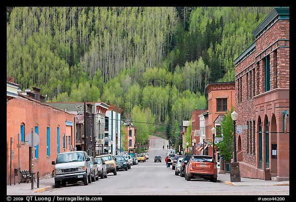 Historic brick buildings and slope with newly leafed aspens. Telluride, Colorado, USA (color)