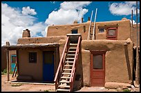 Multi-story pueblo houses with ladders. Taos, New Mexico, USA