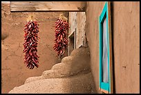 Ristras, adobe walls, and blue window. Taos, New Mexico, USA