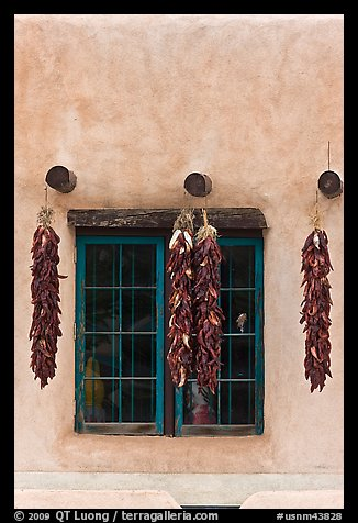 Ristras hanging from vigas and blue window. Taos, New Mexico, USA