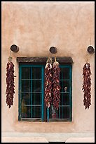 Ristras hanging from vigas and blue window. Taos, New Mexico, USA ( color)