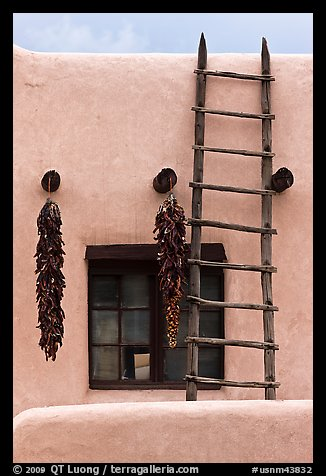 Strings of red peppers and ladder on building in pueblo style. Taos, New Mexico, USA