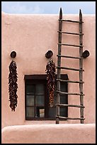 Strings of red peppers and ladder on building in pueblo style. Taos, New Mexico, USA ( color)