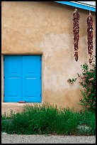 Ristras hanging from roof with blue shutters. Taos, New Mexico, USA