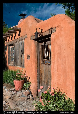 Flowers, adobe wall, and weathered door. Santa Fe, New Mexico, USA (color)