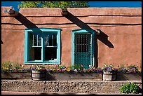 Adobe facade with flowers, windows, and vigas shadows. Santa Fe, New Mexico, USA (color)