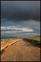 Dirt road under storm clouds. New Mexico, USA