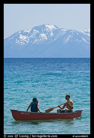 Man and woman in canoe with snowy mountains in the background, Lake Tahoe, Nevada. USA (color)