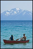 Man and woman in canoe with snowy mountains in the background, Lake Tahoe, Nevada. USA ( color)