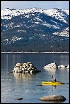Kayaker with backdrop of snow-covered mountains, Lake Tahoe-Nevada State Park, Nevada. USA