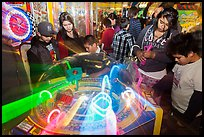 Family plays arcade game with spining lights. Reno, Nevada, USA (color)