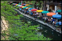 Tables under colorful umbrellas next to canal. San Antonio, Texas, USA ( color)