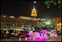 Horse carriages and Tower Life Building at night. San Antonio, Texas, USA ( color)