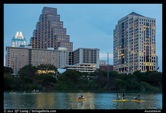 Water pedaling in front of skyline at dusk. Austin, Texas, USA (color)