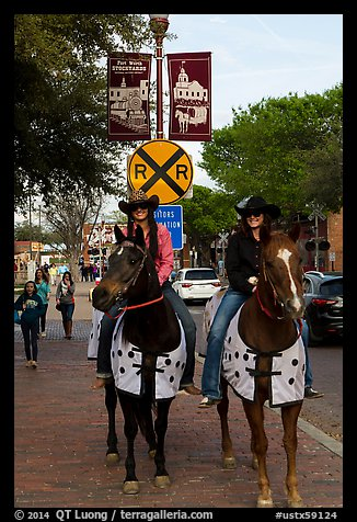 Women riding horses on sidewalk, Stockyards. Fort Worth, Texas, USA (color)