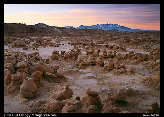 Goblins and snowy mountains at sunrise, Goblin State Park. Utah, USA