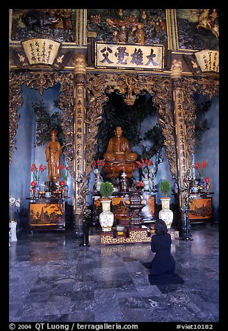 Woman praying at the altar. Ho Chi Minh City, Vietnam