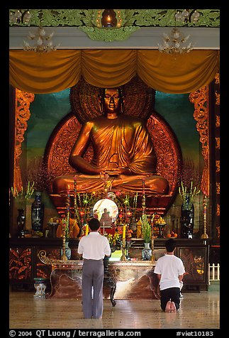 Men worshipping in front of a large Buddha state, Xa Loi pagoda. Ho Chi Minh City, Vietnam