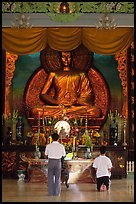 Men worshipping in front of a large Buddha state, Xa Loi pagoda. Ho Chi Minh City, Vietnam (color)