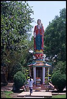 Woman praying under a large buddhist statue. Ho Chi Minh City, Vietnam (color)