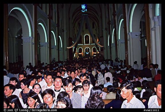 Crowds exit the Cathedral St Joseph at the end of the Christmas mass. Ho Chi Minh City, Vietnam (color)