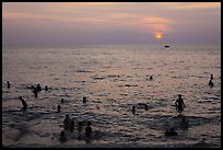 People bathing in Gulf of Thailand waters at sunset. Phu Quoc Island, Vietnam ( color)