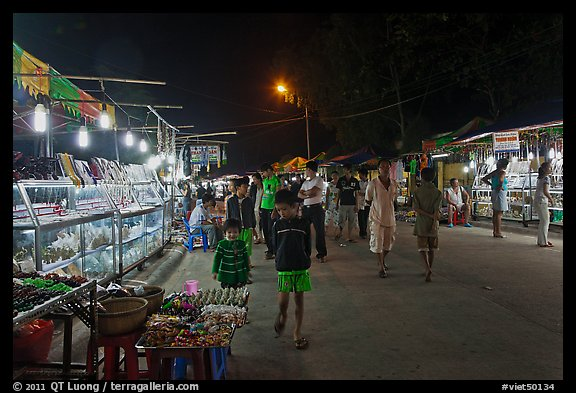Shoppers walk past craft booth at night market. Phu Quoc Island, Vietnam (color)