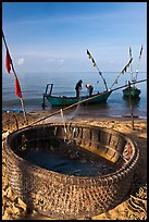 Fishermen pulling net out of circular basket. Phu Quoc Island, Vietnam ( color)