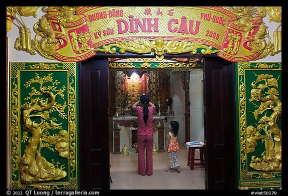 Woman with girl worshipping at Dinh Cau temple, Duong Dong. Phu Quoc Island, Vietnam (color)