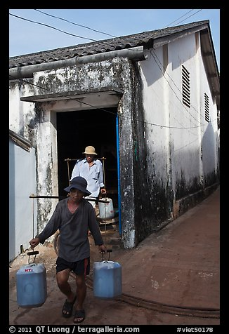 Workers carrying out containers of nuoc mam, Duong Dong. Phu Quoc Island, Vietnam (color)