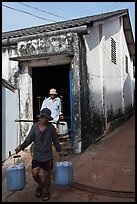 Workers carrying out containers of nuoc mam, Duong Dong. Phu Quoc Island, Vietnam ( color)
