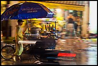 Man riding riding food cart in the rain. Ho Chi Minh City, Vietnam (color)