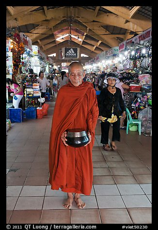 Buddhist Monk doing alms round in Ben Thanh Market. Ho Chi Minh City, Vietnam (color)
