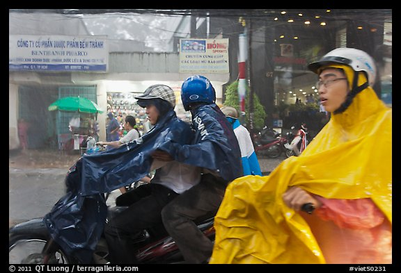Motorcycle riders during afternoon mooson. Ho Chi Minh City, Vietnam